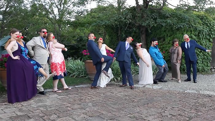 Tuscany wedding videographer: The bride and groom doing a funny photo with their guests